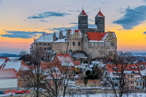 Das Quedlinburger Schloss und Stiftskirche im Winter beim Sonnenuntergang